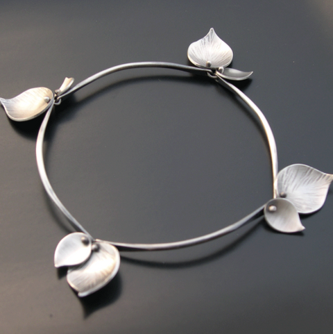 A silver bracelet with pieces that look like leaves