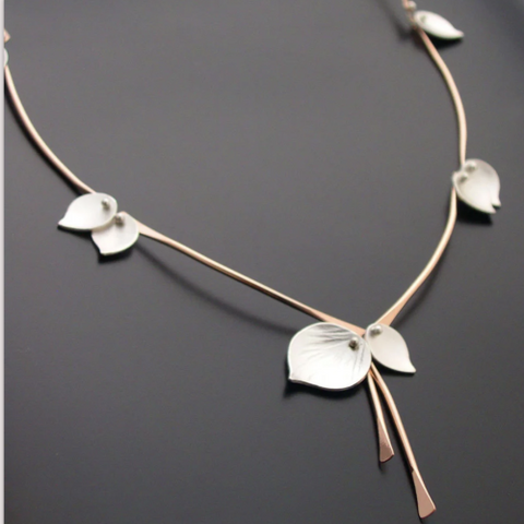 A gold and silver necklace with pieces that look like aspen leaves