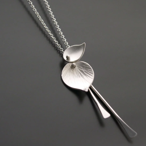 A silver necklace with pieces that look like aspen leaves