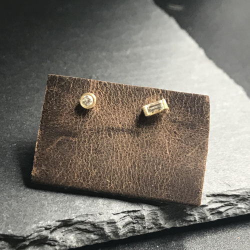 these petite minimalist modern earrings feature mismatched diamond (.12cts) studs are set in 14k yellow gold