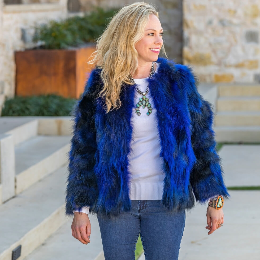 Woman smiling wearing cobalt blue fox fur bolero