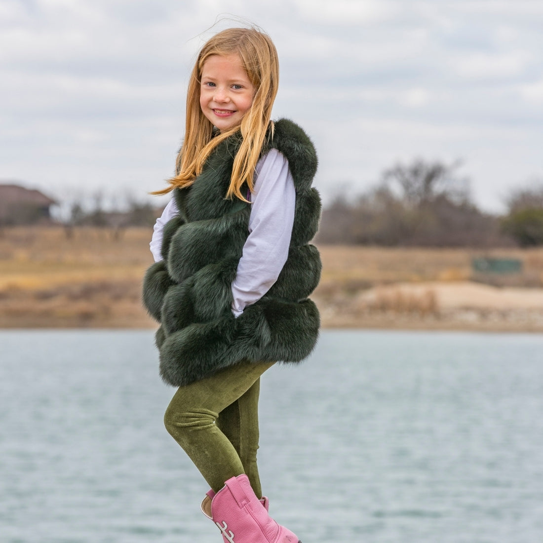 Little girl wearing emerald green fox fur vest