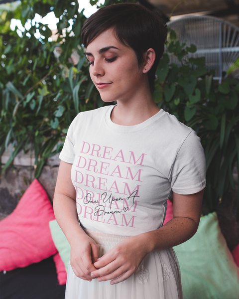 Short haired girl wearing the DREAM tshirt. The shirt is a Sleeping Beauty Inspired White Tshirt with Dream in pink repeated on the front then over the top in a handwritten style Once upon a dream