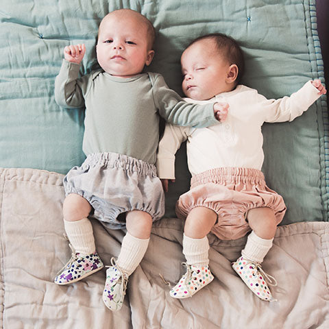 newborn twins in Amy and Ivor lace up baby shoes spots and flower prints uk baby fashion coco and wolf baby bloomers camomile london baby quilts