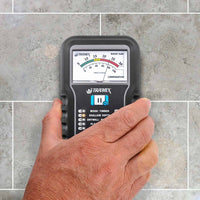 Photo of male hand holding a Tramex ME5 over floor tiles