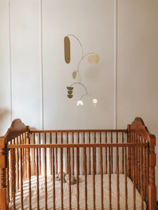 brass baby mobile, hanging mobile, cute baby in a cot, baby laughing at a mobile, handmade brass mobile, modern nursery ideas, nursery design