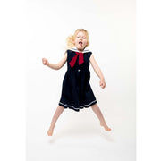 girl in sailor dress jumping