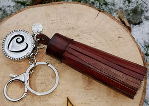 Hand-made brown genuine leather tassel, stainless steel keychain and clip, and 316L stainless steel magnetic locket with Om symbol for diffusing your favorite oils, accented with an ō charm