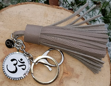 Hand-made gray genuine leather tassel, stainless steel keychain and clip, and 316L stainless steel magnetic locket with Om symbol for diffusing your favorite oils, accented with an ō charm