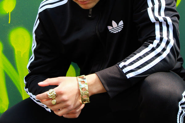 A man wearing a tracksuit and jewellery