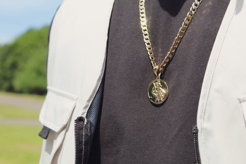 A close up of a pendant on a gold chain