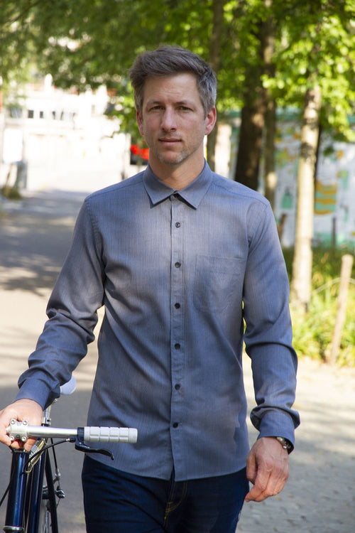 man wearing a merino wol shirt with chest pocket in navy blue holding a bike in the city