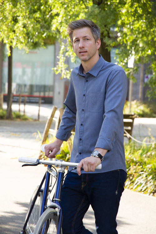 man wearing a merino wol shirt in navy blue holding a bike in the city