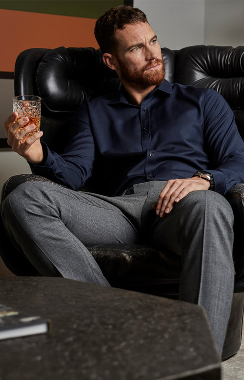 man sitting down and wearing merino wol shirt in navy blue color with long sleeves from Wolk