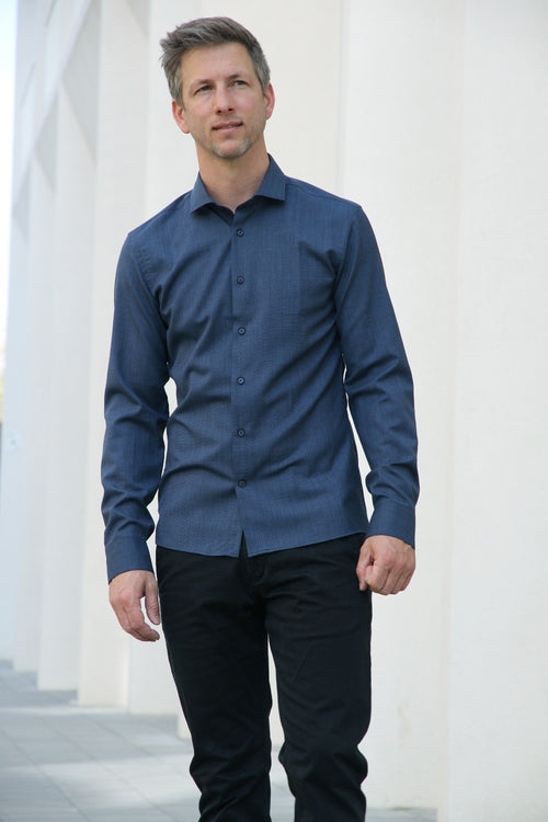 man wearing a navy coloured merino wool shirt with long sleeves from Wolk