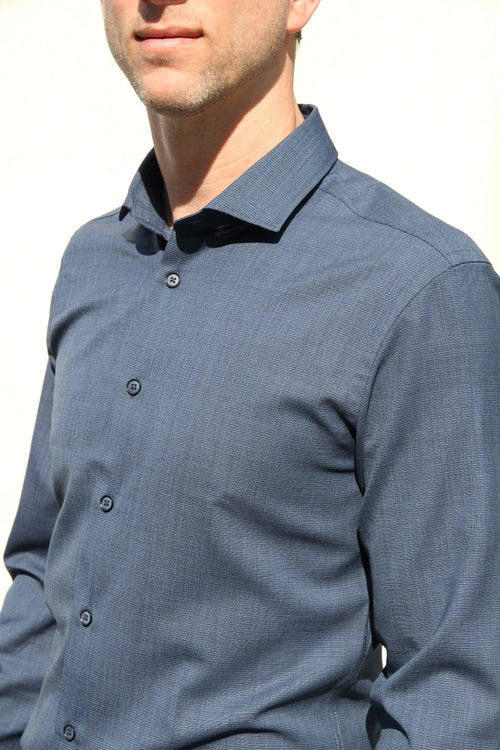 man wearing a navy coloured merino wool shirt with spread collarfrom Wolk