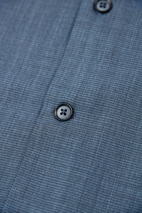 button detail of a navy coloured merino wool shirt from Wolk