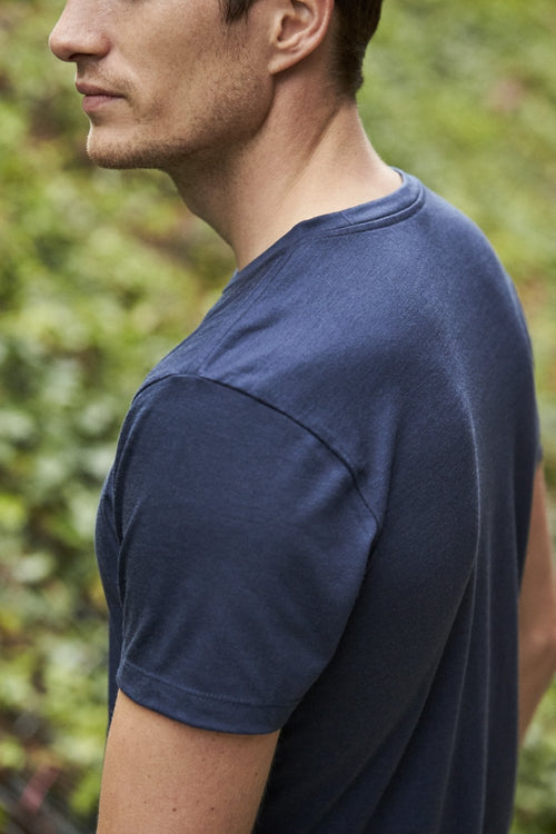 Sideview of man wearing merino wol T-shirt with short sleeves in navy blue color