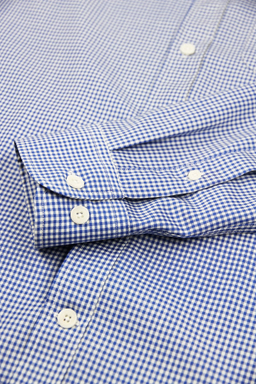 cuff detail of merino wool shirt in blue gingham with white corozo buttons