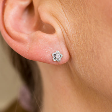 These pretty 9ct white gold stud earrings are set with round brilliant cut diamonds.  The floral design is delicate and very attractive. 9ct white gold
