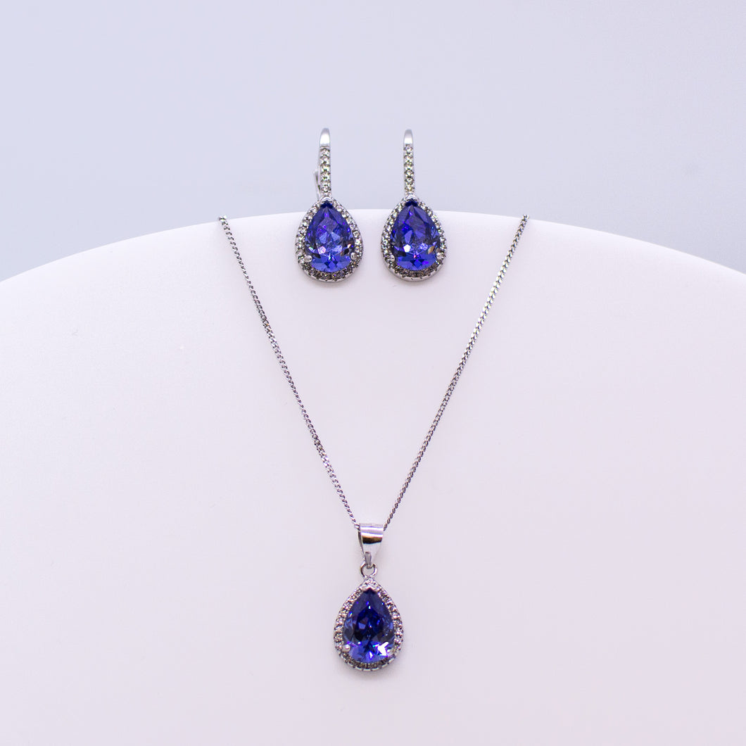These sterling silver pear shaped drop earrings set with glittering cubic zirconia stones in created Tanzanite and white accompanied by the matching necklace are the perfect addition to any outfit. Product details: Product materials: 925 sterling silver, cubic zirconia Chain length: 44cm inch fine diamond cut curb chain Pendant dimensions:  20mm L x 10mm W Earring dimensions:  24mm L x 10mm W Drop earrings with integrated CZ set German wires.