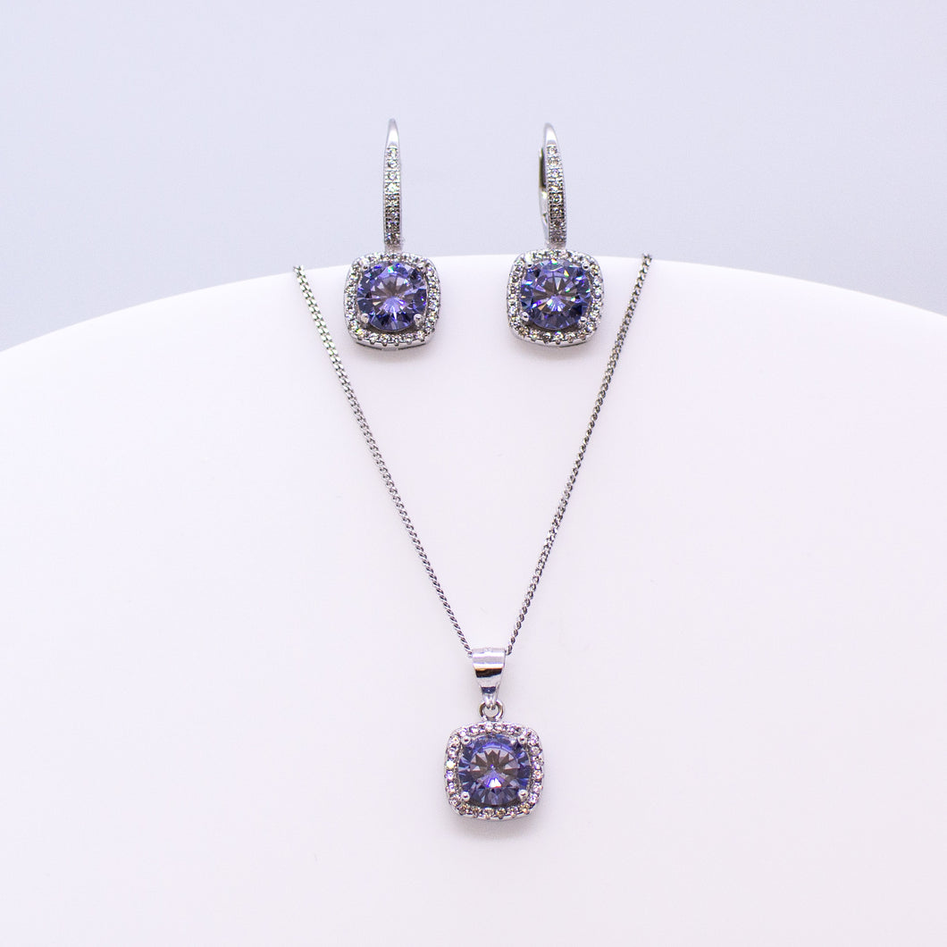 These sterling silver cushion shaped drop earrings set with glittering cubic zirconia stones in created Tanzanite colour and white accompanied by the matching necklace are the perfect addition to any outfit. Product details: Product materials: 925 sterling silver, cubic zirconia Chain length: 44cm inch fine diamond cut curb chain Pendant dimensions:  18mm L x 10mm W Earring dimensions:  22mm L x 10mm W Drop earrings with integrated CZ set German wires.