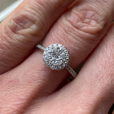 This round cluster diamond engagement ring  is a complete classic.  Its simplicity is so romantic. The Details... One 18ct white gold diamond engagement ring.  Diamond halo cluster with very slightly tapered diamond-set shoulders. 0.75ct in total of round brilliant cut diamonds.  Colour GH.  Clarity SI. 18ct white gold, Pure White (tm) nickel-free.  Size N.