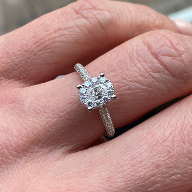 This oval cluster diamond engagement ring  is a complete classic.  Its simplicity is so romantic. The Details... One 18ct white gold diamond engagement ring.  Diamond halo cluster in an oval shape with pavé diamond-set shoulders. 0.79ct in total of diamonds.  Colour G.  Clarity VS. Centre stone: 0.23ct Melée: 0.56ct 18ct white gold.  Size N.