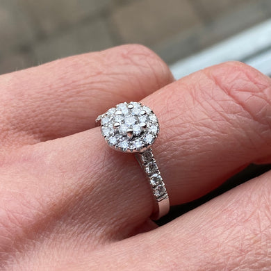 This round cluster diamond engagement ring  is a complete classic.  Its simplicity is so romantic. The Details... One 18ct white gold diamond engagement ring.  Diamond halo cluster with diamond-set shoulders. 0.66ct in total of round brilliant cut diamonds.  Colour GH.  Clarity SI. 18ct white gold, Pure White (tm) nickel-free.  Size N.