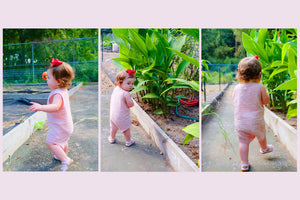 Toddler girl walking next to green trees wearing pink organic bodysuit