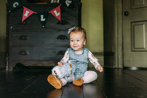 Baby girl smiling with her owl stuff animal on wooden floor