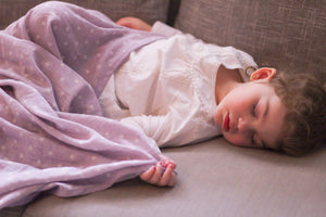 Toddler girl sleeping on couch covered with purple polka dot blanket