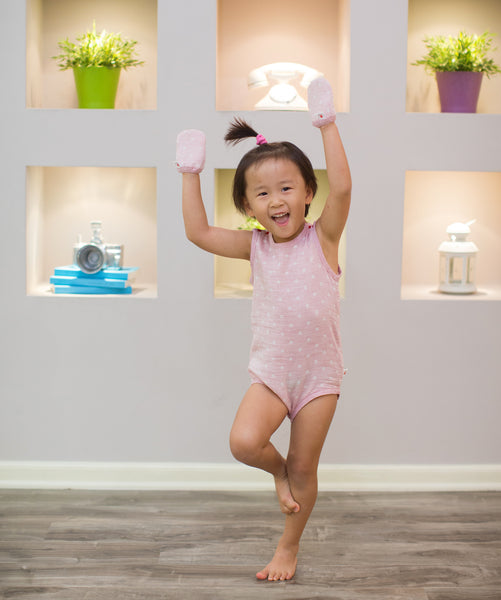 Toddler girl with eczema posting ballerina wearing Pokka Kids 100 % GOTS certified organic cotton baby bodysuit in pink