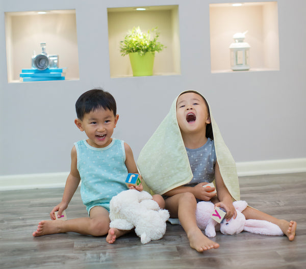 Toddler boy and girl with eczema wearing Pokka Kids 100 % GOTS certified organic cotton baby bodysuits smiling on floor