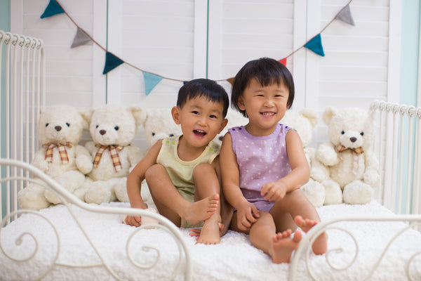 Toddler boy and girl with eczema wearing Pokka Kids 100 % GOTS certified organic cotton baby bodysuits smiling on day bed