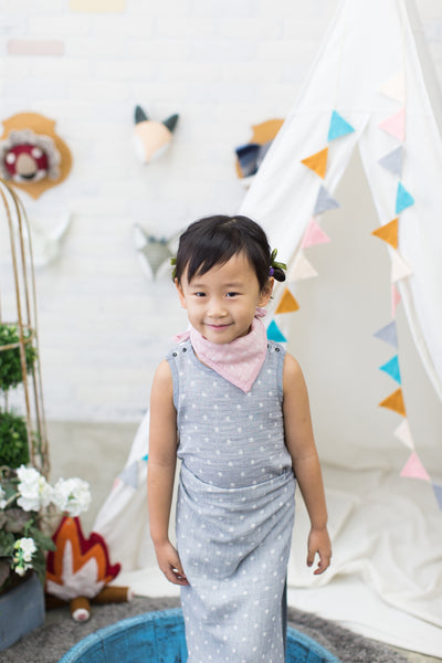 Toddler girl wearing GOTS Certified organic cotton polka dot bandana bib in pink, bodysuit, and blanket as sarong in gray