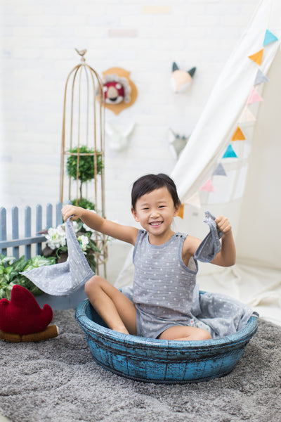 Cute toddler girl playing with charcoal GOTS certified organic cotton hanky while wearing Pokka Kids sleeveless bodysuit