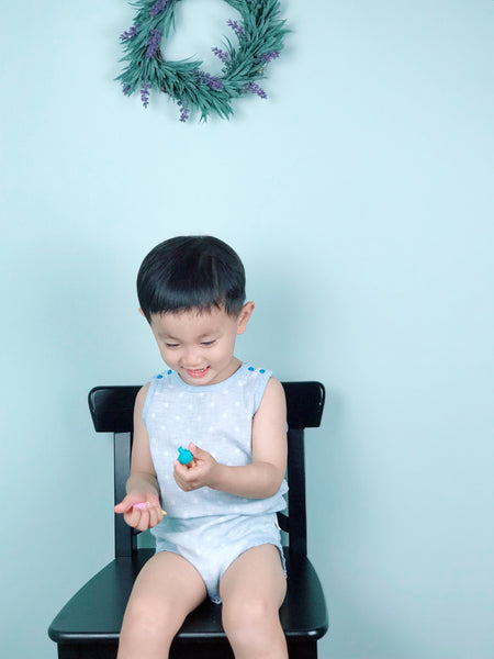 Toddler boy wearing blue GOTS certified organic cotton sleeveless baby bodysuit sitting on a chair