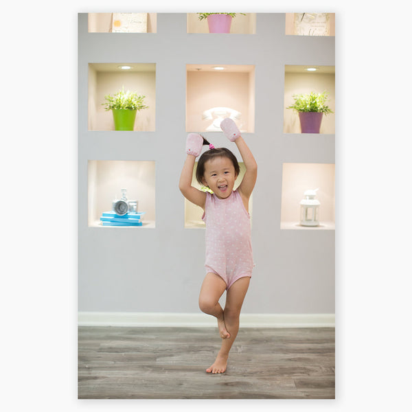 baby girl posing ballerina wearing pink GOTS certified organic cotton bodysuit and mittens designed for eczema