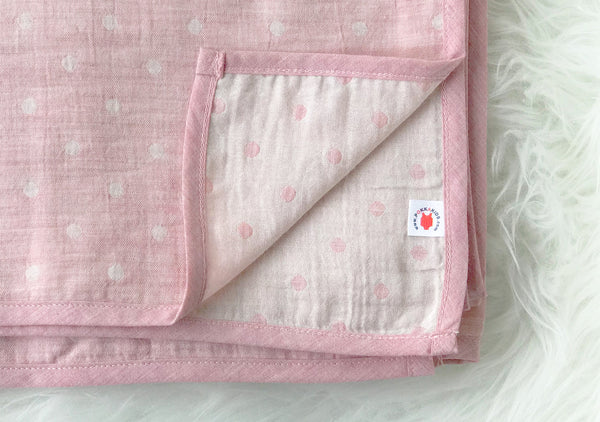 Folded pink GOTS certified organic cotton blanket in Versatile size for use as a stroller cover, or nursing cover