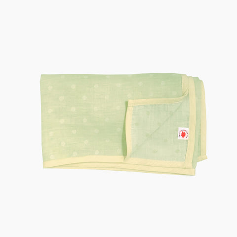 Folded lime polka dot GOTS certified organic cotton blanket for use as a stroller cover, or nursing cover