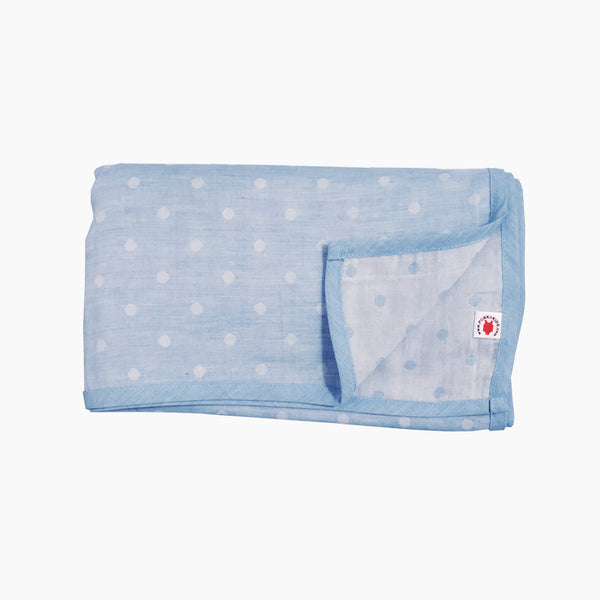 Folded blue polka dot GOTS certified organic cotton blanket for use as a stroller cover, or nursing cover