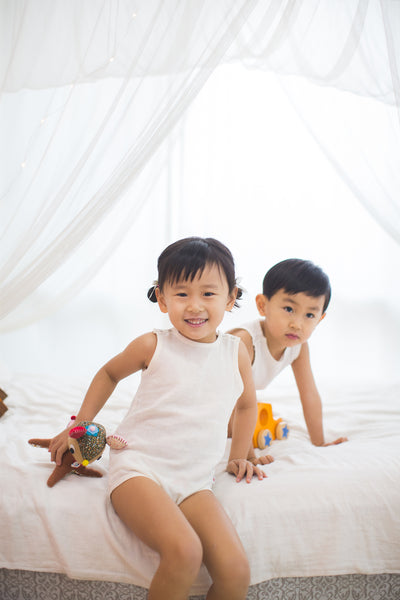 toddler boy and girl smile wearing dye free GOTS certified organic cotton bodysuit sitting on bed