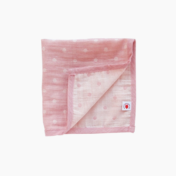 Folded pink GOTS certified organic cotton hanky for use as a wash cloth, burp cloth, bib, scarf or security blanket