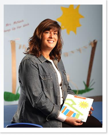 Smiling Teacher holding a Pre-K Letter Learning Lesson