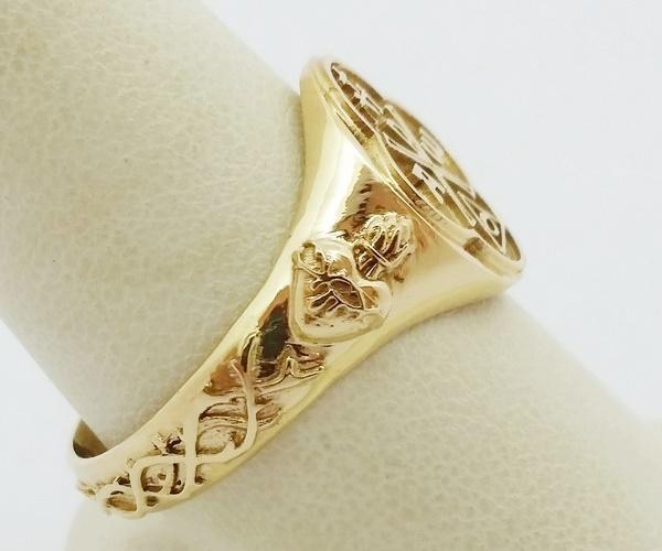 engravings on the side of the gold catholic ring