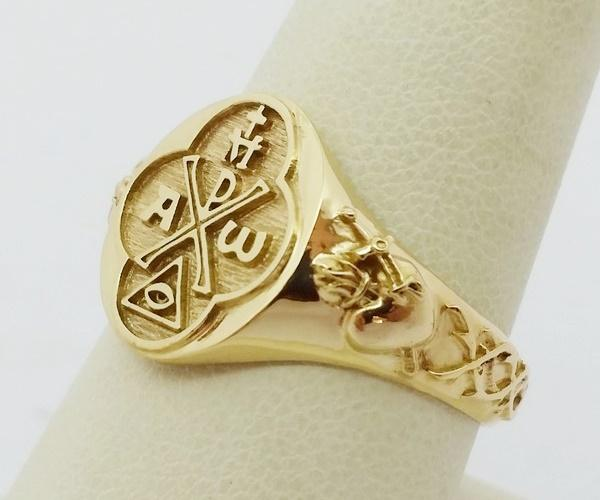 view of the gold ring with all the catholic symbols molded