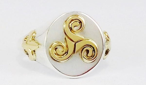 celtic silver ring with gold triskele on the plateau