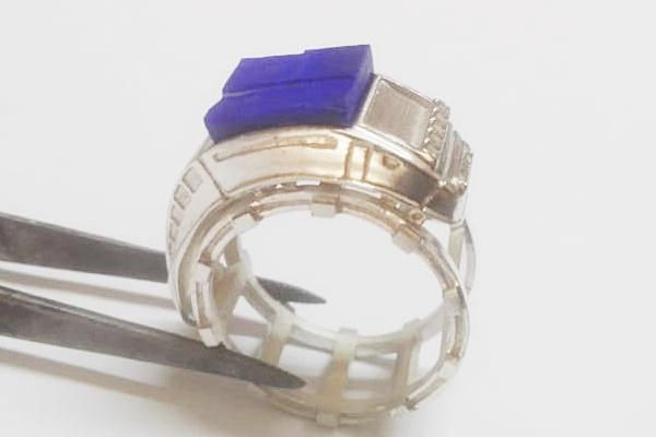 rough lapis lazuli set on silver ring being made
