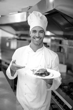 Chef smiling with plate of food.